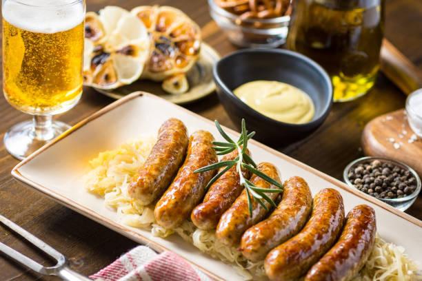 gegrillte würstchen mit krautsalat, senf und bier. bratwurst und sauerkraut. - bratwurst mit sauerkraut stock-fotos und bilder