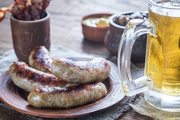 grilled sausages with fried bacon rashers and mushrooms - german culture stock pictures, royalty-free photos & images