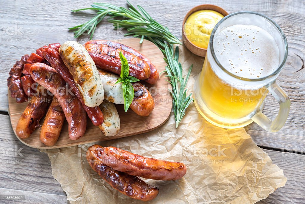 Grilled sausages with glass of beer stock photo