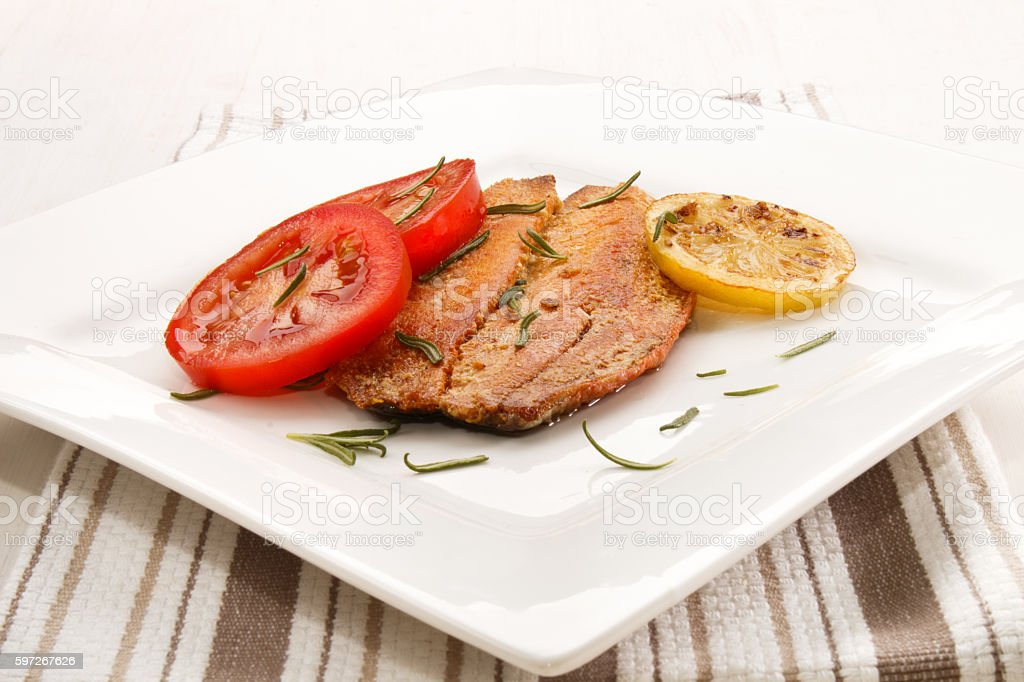 grilled scottish kipper with rosemary, tomato and slice lemon royalty-free stock photo