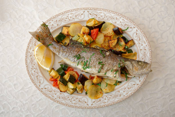 Grilled sea bass with baked vegetables stock photo