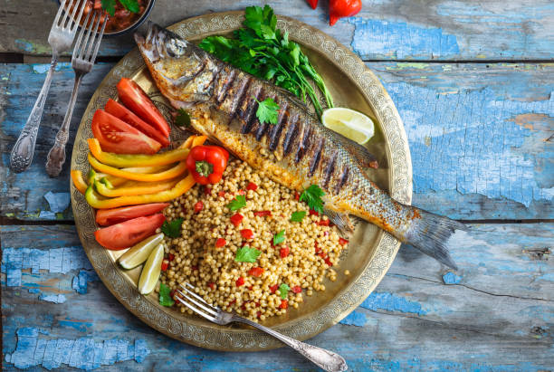 Grilled sea bass with ptitim and vegetables on copper plate, copy space stock photo