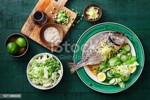 Grilled sea bream with fresh vegetables, herbs, ginger and Chinese broth
