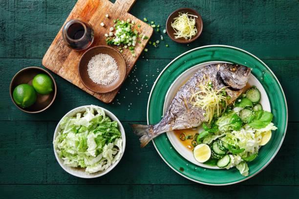 Grilled sea bream with vegetables Grilled sea bream with fresh vegetables, herbs, ginger and Chinese broth perch fish stock pictures, royalty-free photos & images