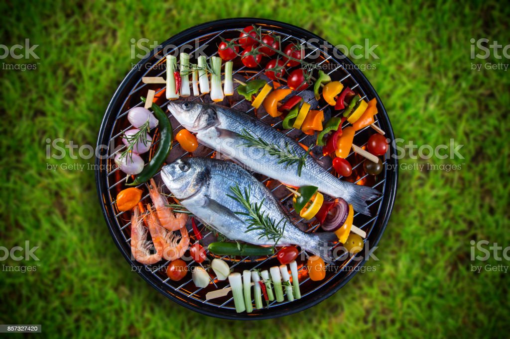 Grilled sea fishes with vegetable, skewers and prawns on a barbecue grill stock photo