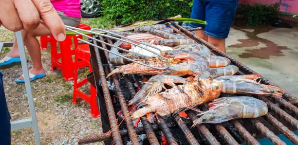 gegrillte meeresfrüchte ist frische garnelen, tintenfisch und roter fisch auf kohle-herd. party feiern der familie, urlaub. - küstenfamilienzimmer stock-fotos und bilder