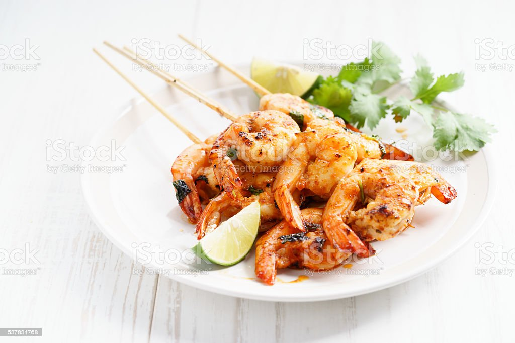 grilled shrimp kababs with sriracha and lime stock photo