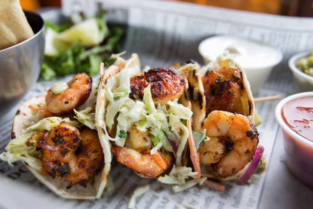 Grilled Shrimp Tacos Grilled jumbo shrimp in corn tortilla tacos with cabbage garnish on an old fashioned newspaper wrapper. main course stock pictures, royalty-free photos & images