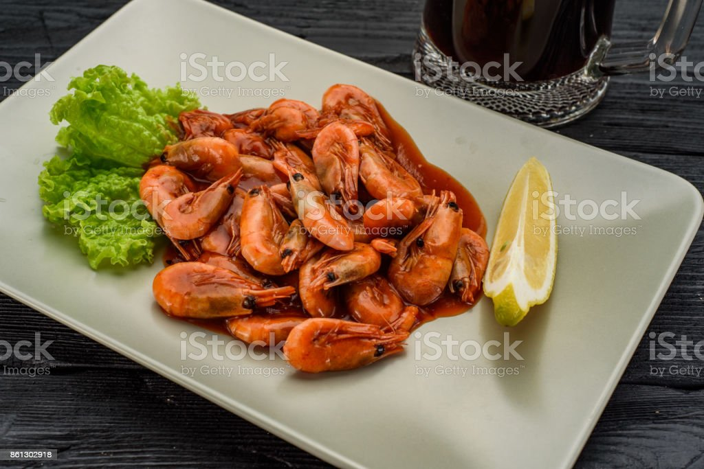 Grilled shrimps and dark beer over wooden table. stock photo