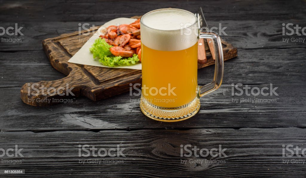 Grilled shrimps on a board and beer mug. stock photo
