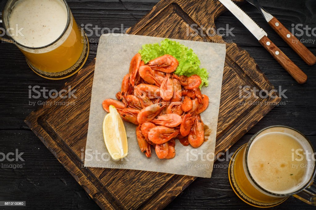 Grilled shrimps on a board and beer mug. Wooden background. stock photo