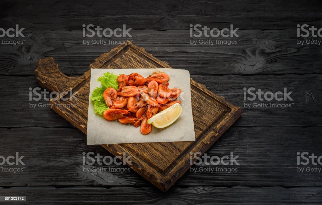 Grilled shrimps on a board over dark wooden background stock photo