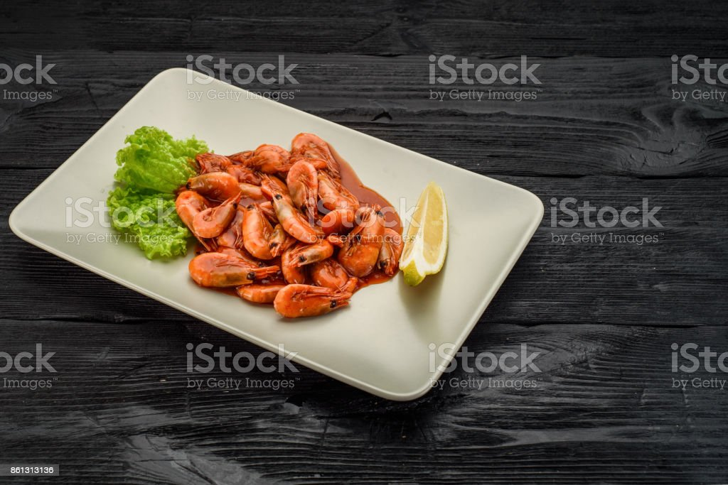 Grilled shrimps on a white table over dark wooden table. stock photo