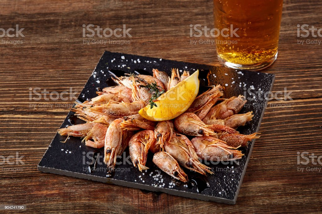 Grilled shrimps on black board pan and beer on wooden table stock photo