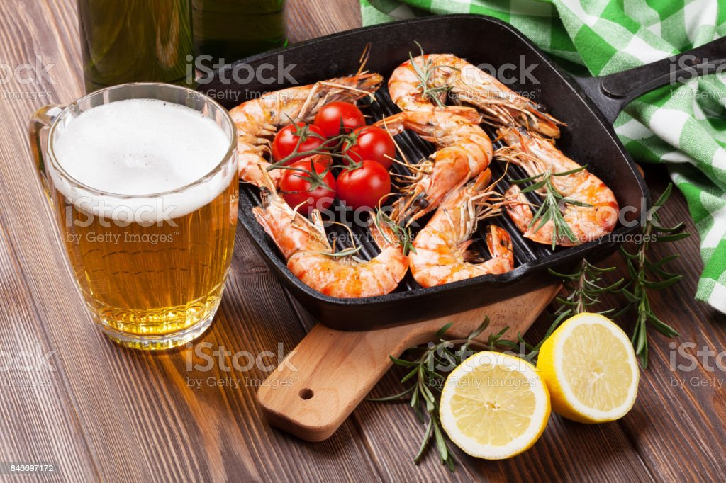 Grilled shrimps on frying pan and beer stock photo