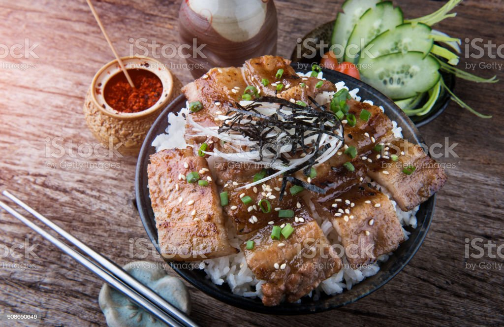 Grilled slice pork with charcoal flame set on rice bowl in Japanese style. stock photo