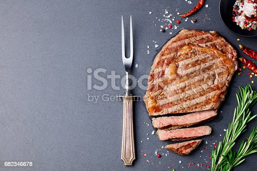 808351106 istock photo Grilled sliced beef steak on slate stone table. Top view. Copy space 682346678