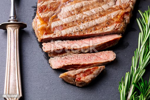 808351106 istock photo Grilled sliced beef steak on slate stone table. Top view. 682346852