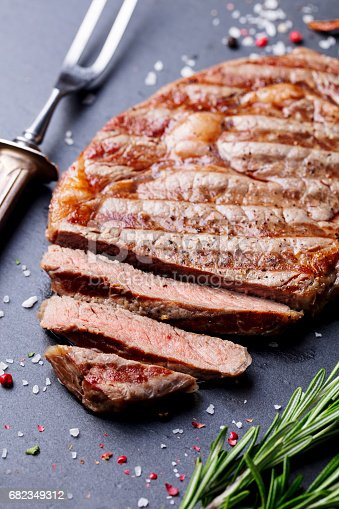 808351094 istock photo Grilled sliced beef steak on slate stone table. Top view. 682349312