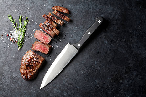 Grilled sliced beef steak Grilled sliced beef steak on stone table. Top view with copy space kitchen knife stock pictures, royalty-free photos & images