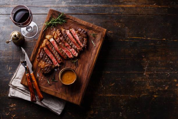gegrilde gesneden biefstuk rib-eye met pepersaus - vleesdelen stockfoto's en -beelden