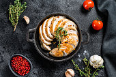 Grilled sliced Turkey steaks in a pan. Breast fillet. Black background. Top view.