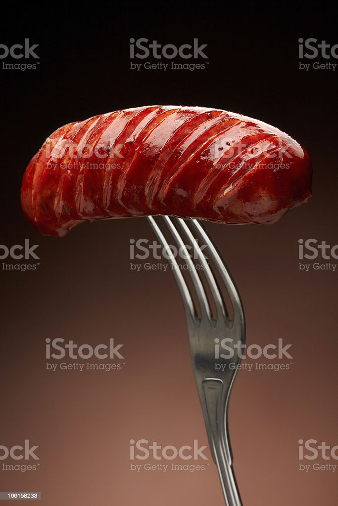 Grilled smoked sausage on a fork royalty-free stock photo