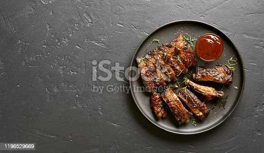 Spicy hot grilled spare ribs on plate over black stone background with copy space. Tasty bbq meat. Top view, flat lay