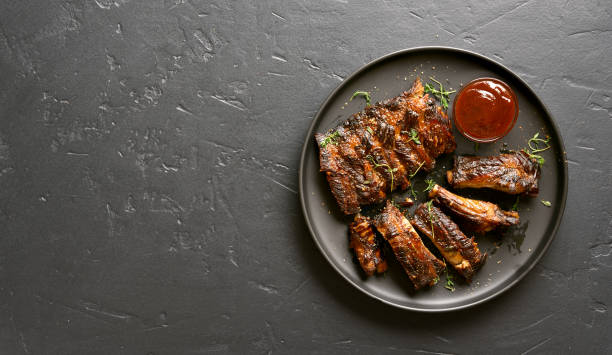 Grilled spare ribs Spicy hot grilled spare ribs on plate over black stone background with copy space. Tasty bbq meat. Top view, flat lay pork stock pictures, royalty-free photos & images