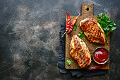 Grilled spicy chicken breast with ketchup on a wooden cutting board over dark slate, stone, concrete or metal background.Top view with copy space.