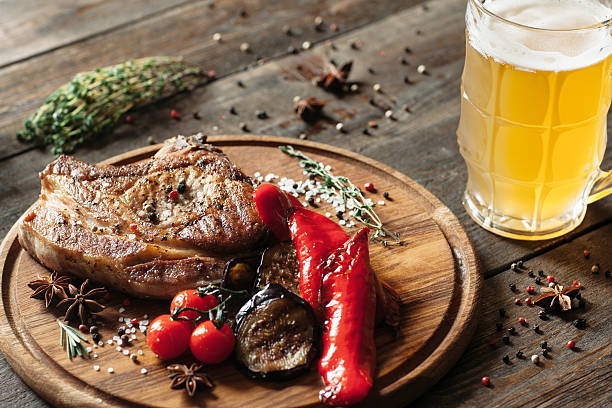 Grilled steak and beer on wooden background stock photo
