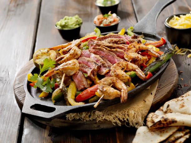 gegrilltes steak und garnelen fajita platte - meeresfrüchte enchiladas stock-fotos und bilder