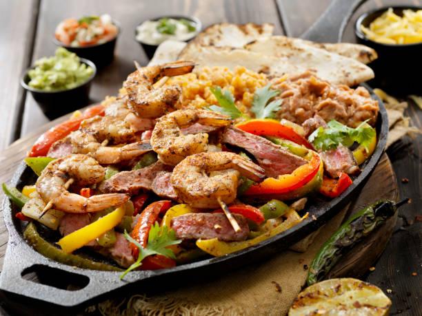 gegrilltes steak und garnelen fajita teller mit reis und wieder gebratene bohnen - meeresfrüchte enchiladas stock-fotos und bilder