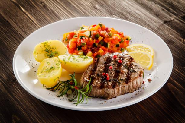 gegrilltes steak, kartoffeln und salat - salzkartoffel stock-fotos und bilder