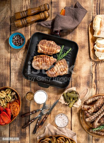 685404620istockphoto Grilled steak, grilled sausages, grilled vegetables and lager beer on the wooden table 646085458