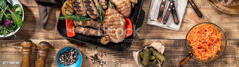 685404620istockphoto Grilled steak, grilled sausages, grilled vegetables on the wooden table 677186742