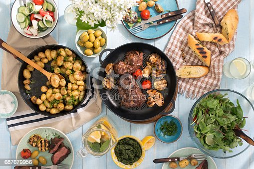 657146780 istock photo Grilled steak, grilled vegetables, potatoes, salad, different snacks and homemade lemonade on blue rustic wooden table 687679956