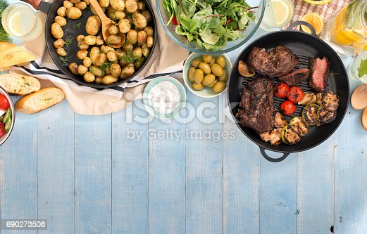 685404620istockphoto Grilled steak, grilled vegetables, potatoes, salad, different snacks and homemade lemonade on blue rustic wooden table with border 690273508
