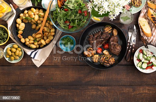685404620istockphoto Grilled steak, grilled vegetables, potatoes, salad, different snacks and homemade lemonade on rustic wooden table with border, top view 690273902