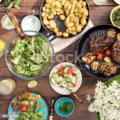 690274036 istock photo Grilled steak, grilled vegetables, potatoes, salad, different snacks and homemade lemonade on rustic wooden table 882782598