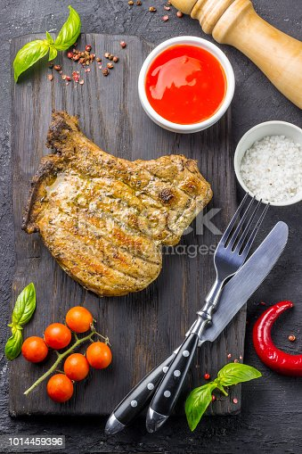 655794674istockphoto Grilled Steak on bone with knife and fork carving 1014459396