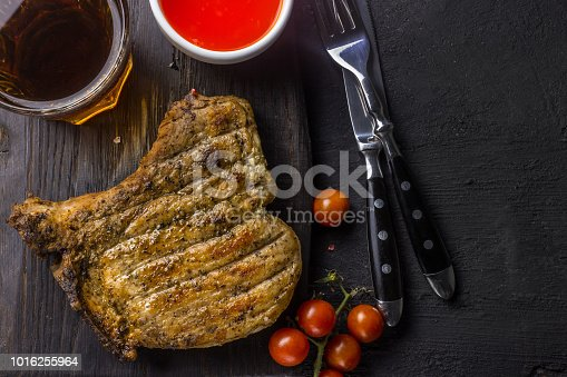 655794674istockphoto Grilled Steak on bone with knife and fork carving 1016255964