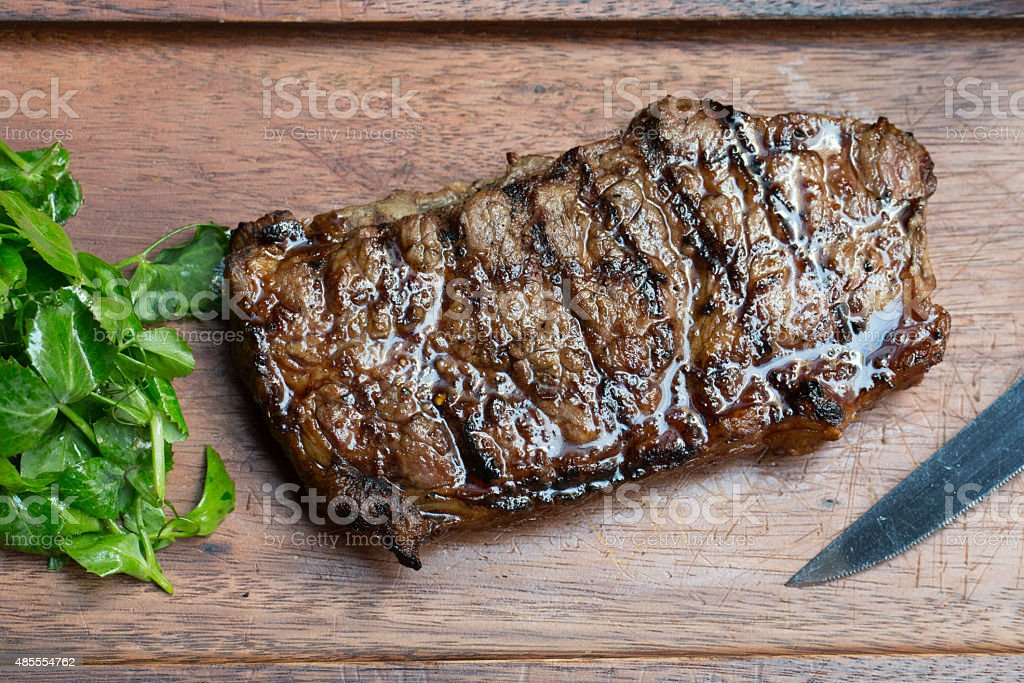 Grilled Steak on Wooden Board stock photo