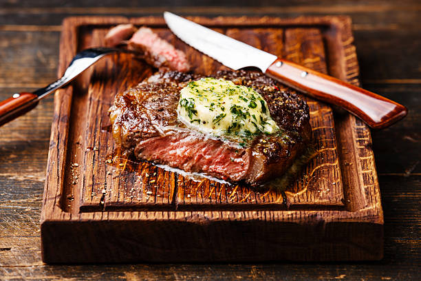 Grilled steak Ribeye with herb butter stock photo