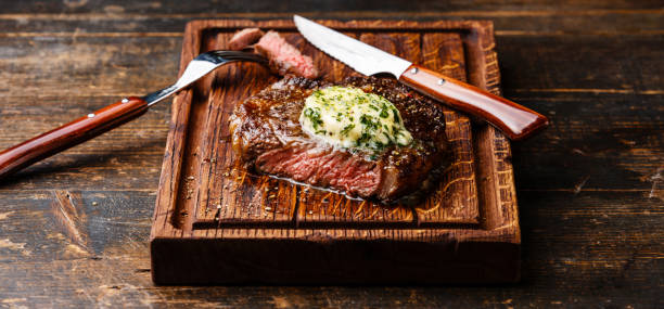 Grilled steak Ribeye with herb butter Grilled Medium rare steak Ribeye with herb butter on cutting board serving size rib eye steak stock pictures, royalty-free photos & images