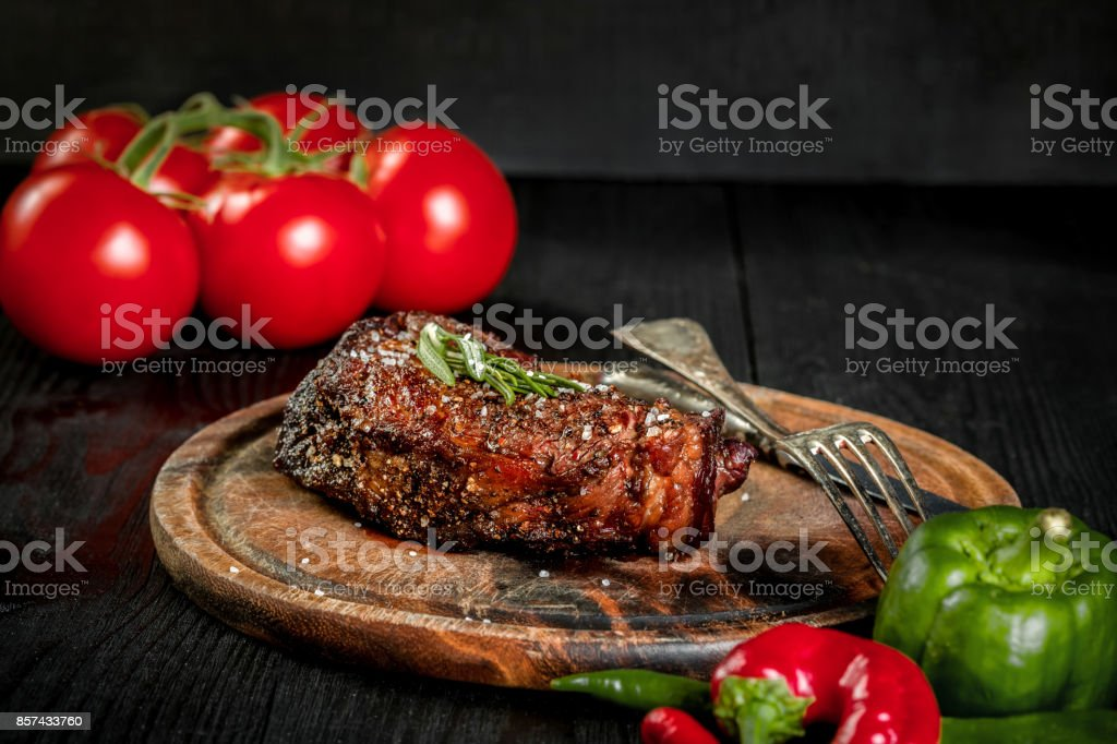 Grilled steak seasoned with spices and fresh herbs served on a wooden board with fresh tomato and red and green peppers stock photo