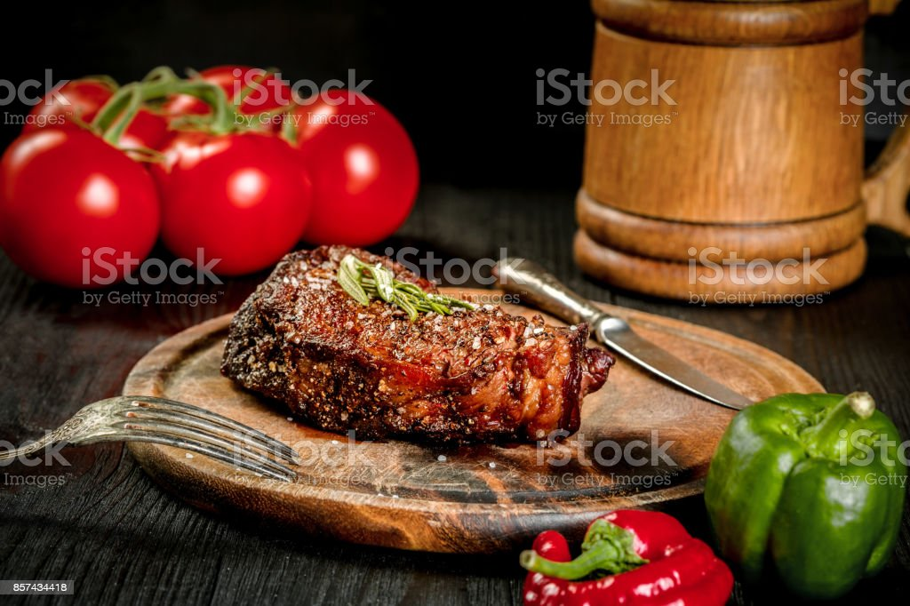Grilled steak seasoned with spices and fresh herbs served on a wooden board with wooden mug of beer, fresh tomato, red and green peppers stock photo