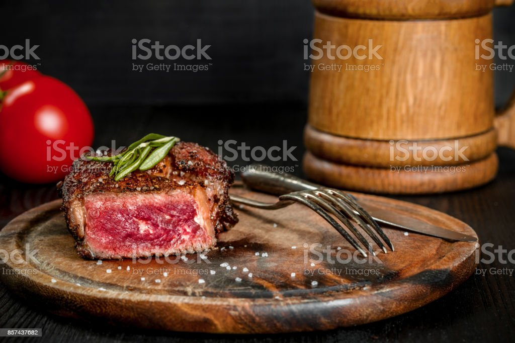Grilled steak seasoned with spices and fresh herbs served on a wooden board with wooden mug of beer and fresh tomato stock photo
