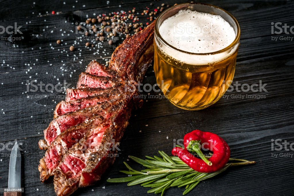 Grilled steak seasoned with spices and fresh herbs served with mug of beer, fresh red pepper stock photo