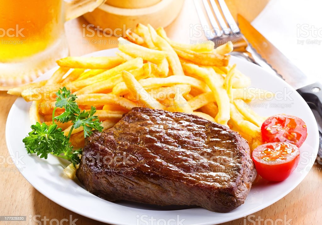 A grilled steak sirloin served with fries and a tomato stock photo